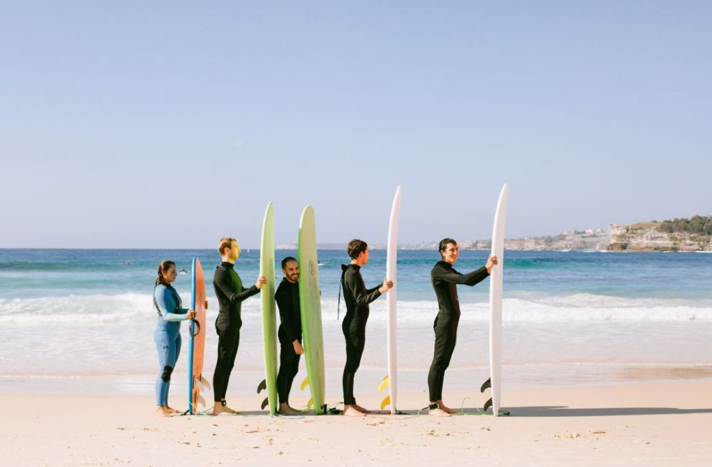 line of people with surfboards