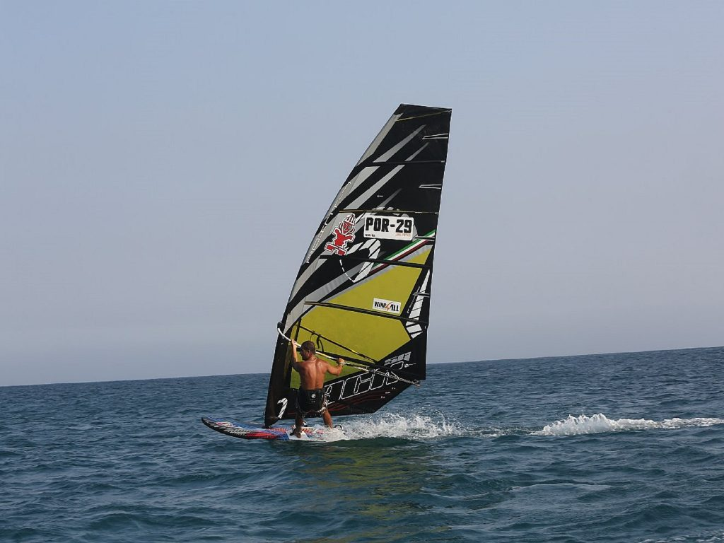 back of a man windsurfing with a black sail