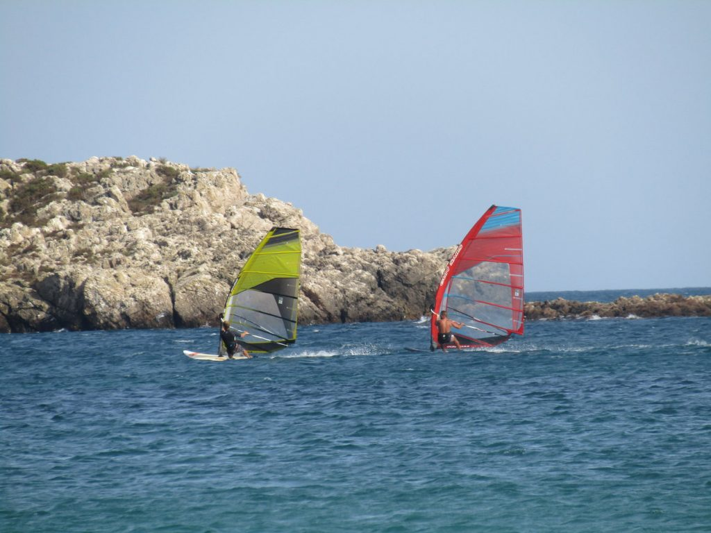 two guys windsurfing to the left