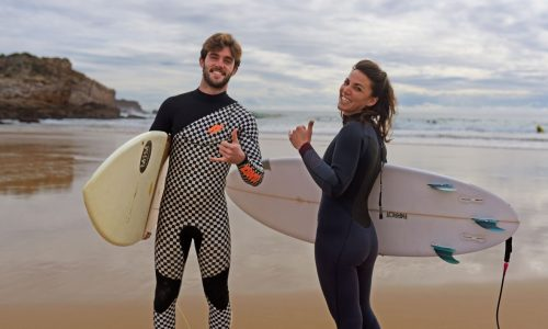 2 surfers holding their board and smiling