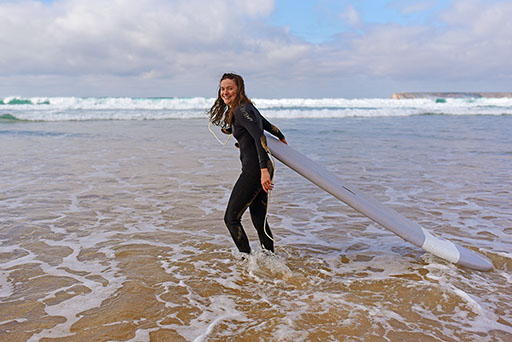 Surfing girl holding her grey board in the water