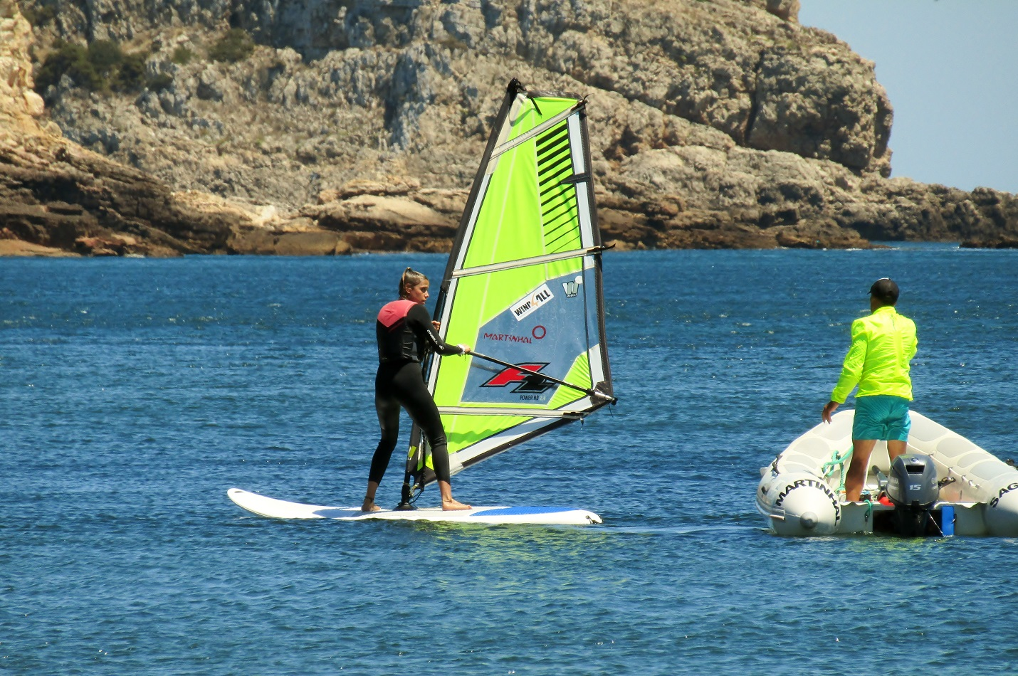 Girl holding her windsurf aside her instructor giving her tips from its boat