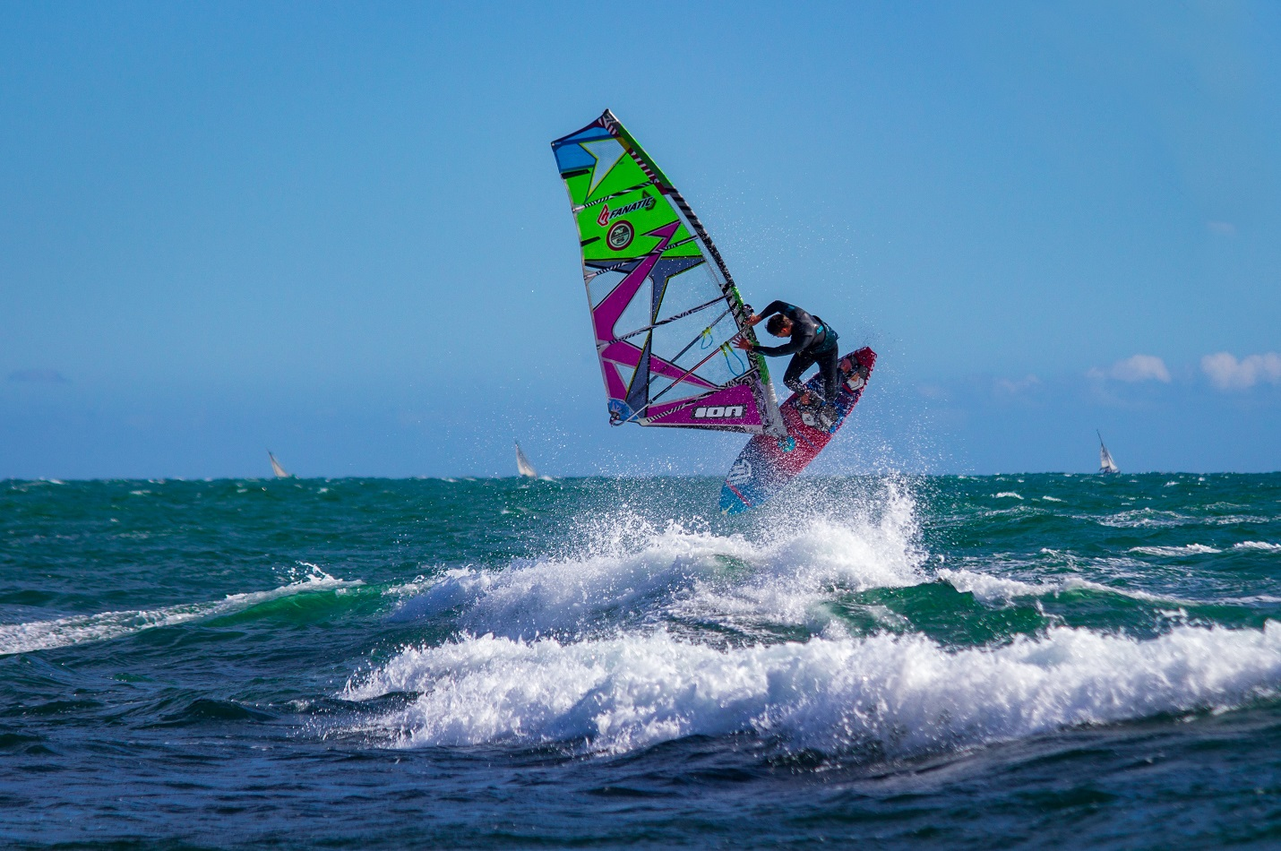 man jumping above a wave with its purple windsurf