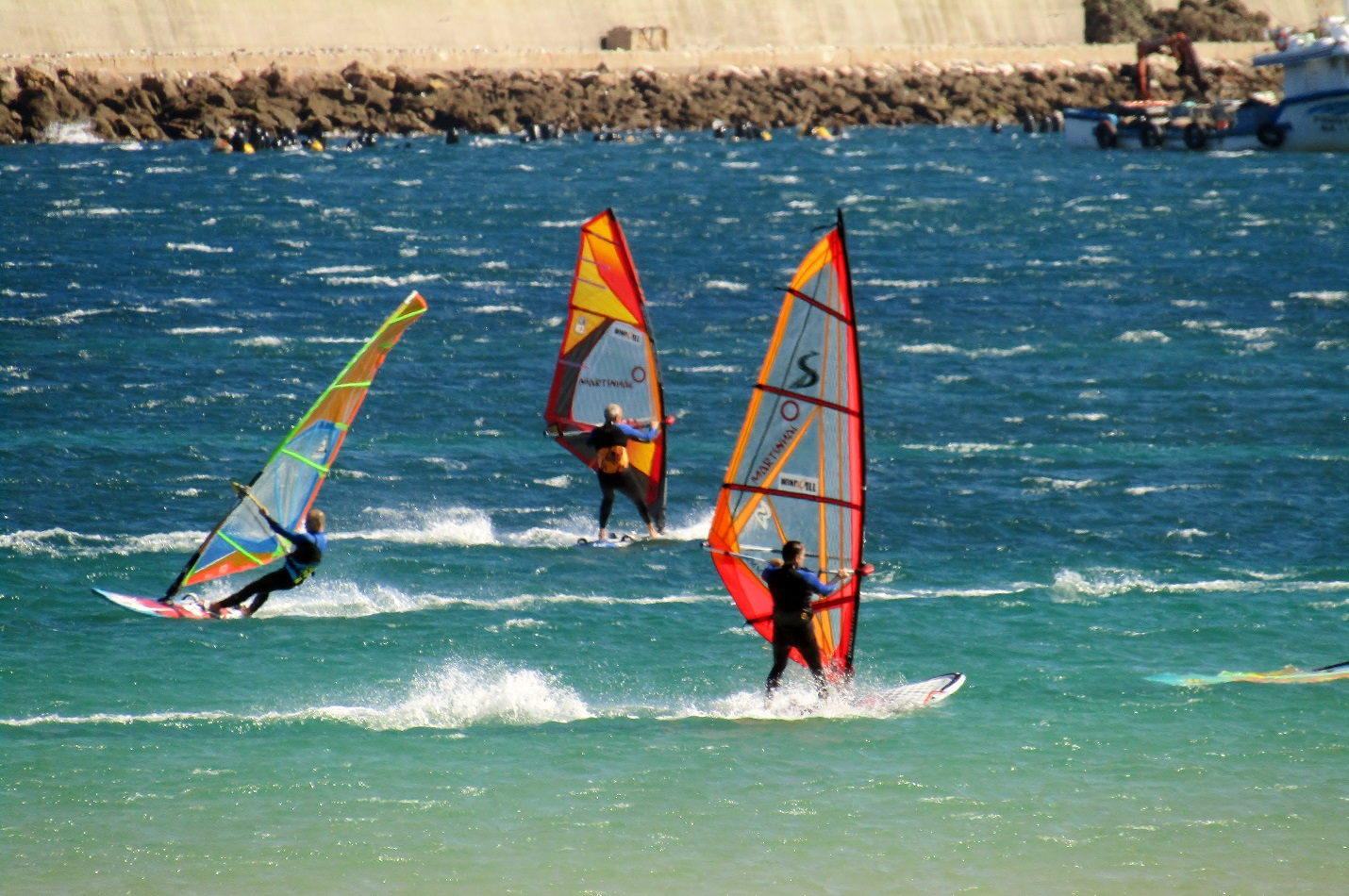 3 windsurfers on the ocean with orange sails