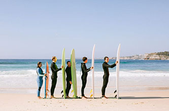 5 people in a row holding their board upright
