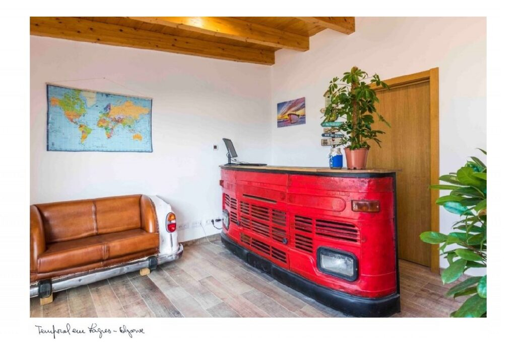 reception of the hostel with a red desk and a vintage sofa