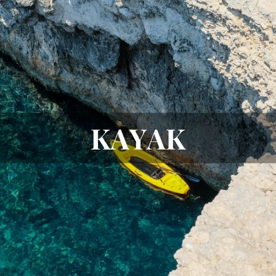 Yellow kayak against a cliff in the ocean