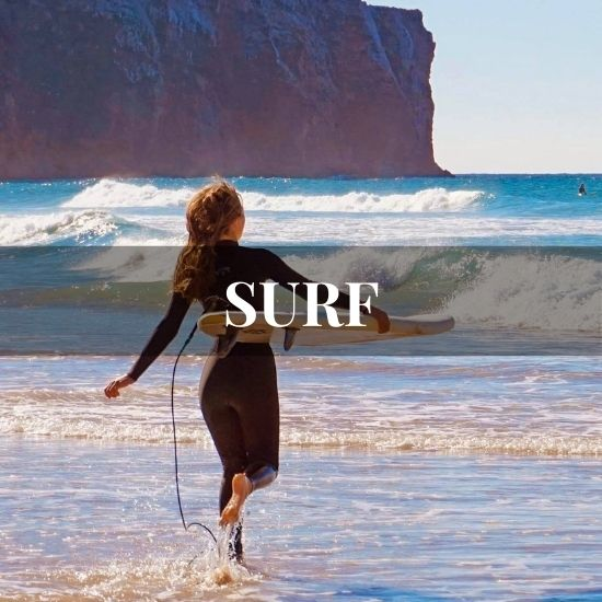 Back of a girl running to the ocean with her surfboard