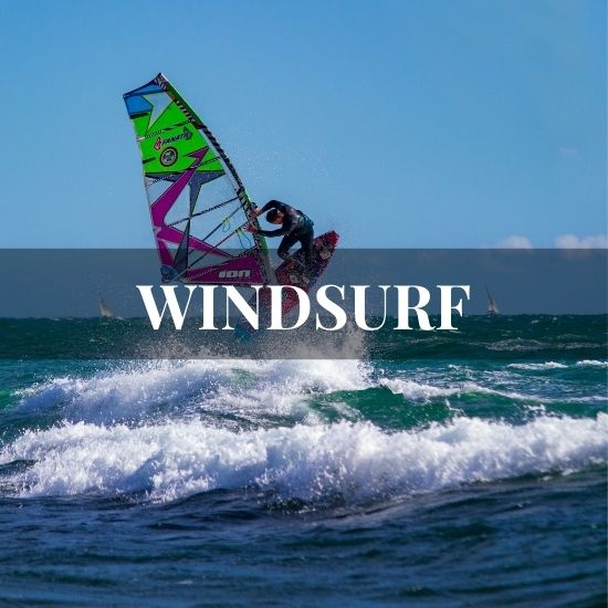 Man jumping with its windsurf board on the ocean