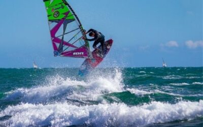 man jumping over a wave with its purple windsurf